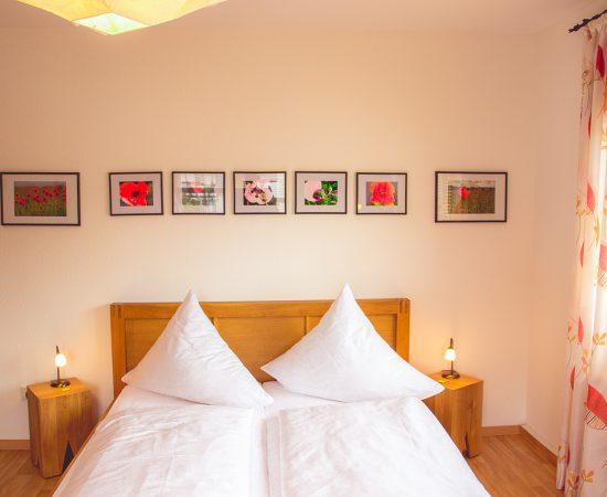 """Zimmer """"Klatschmohnzimmer"""" mit Doppelbett und Klatschmohnfotografien"""