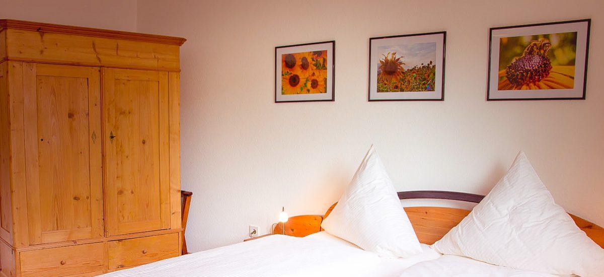 """Zimmer """"Sonnenblumenzimmer"""" mit Doppelbett, Schrank und Sonnenblumenbildern"""