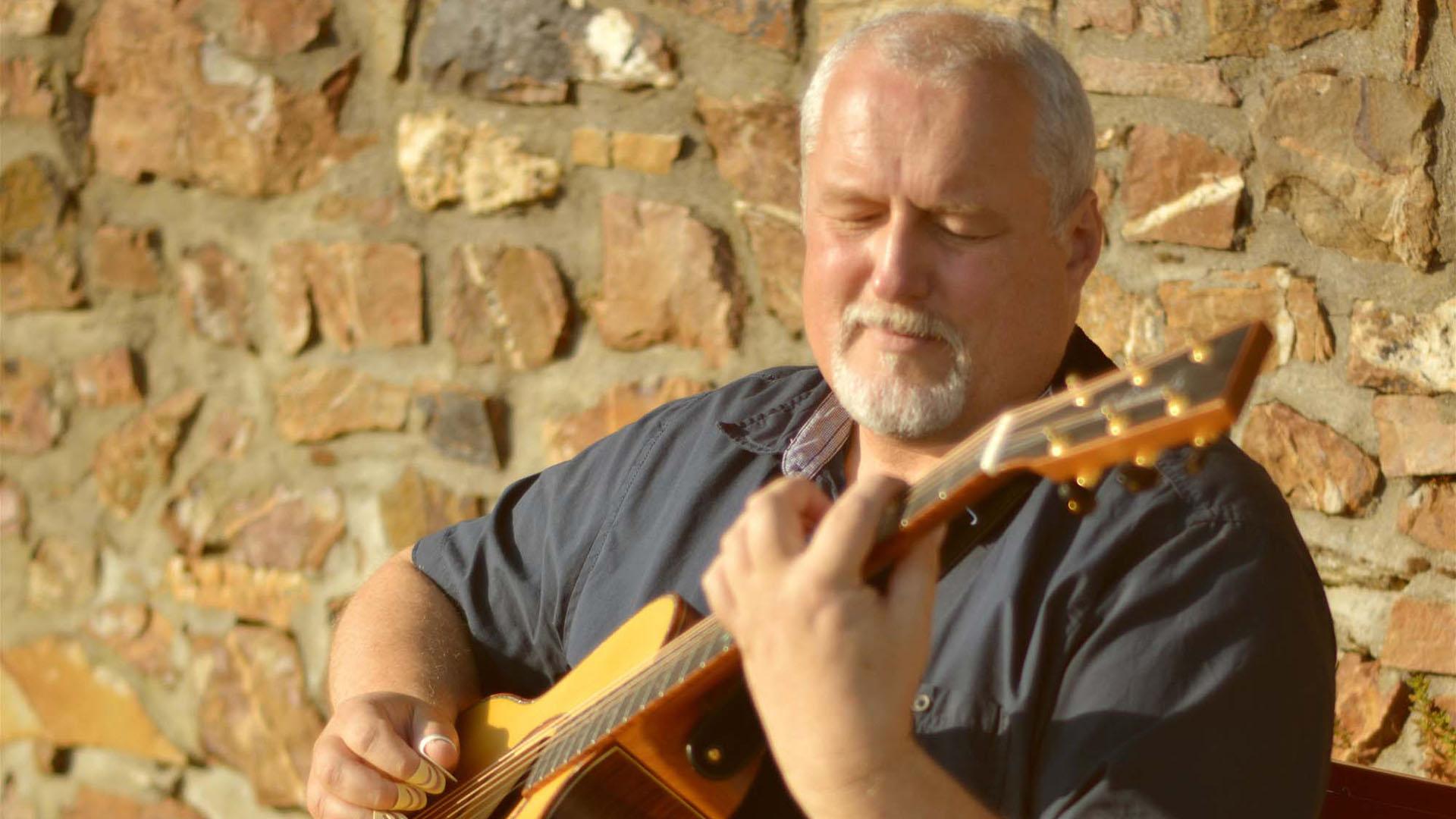 Peter Reimer mit Gitarre vor einer Mauer.