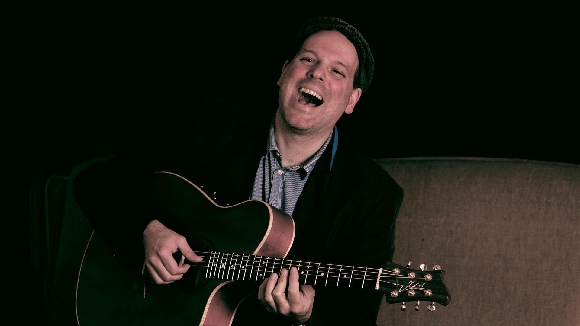 Michael Diehl singend mit Gitarre