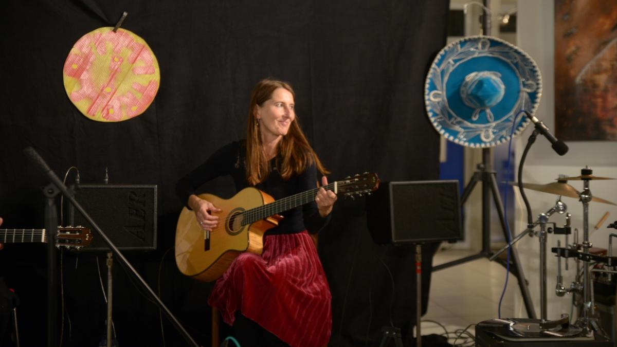 Künstlerin Sabine Schade mit Gitarre bei einem Auftritt des Tri Trallafitti.